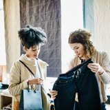 Zwei Frauen schauen sich gemeinsam eine dunkle Jeans an