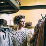 Eine Frau durchsucht Kleidung, die an einer Kleiderstange hängt, in ihrer rechten Hand hält sie ein Oberteil