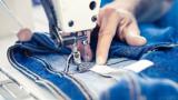 Eine Frau näht ein Paar Jeans, die im Laufe der Produktion durch tausende Hände gehen