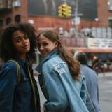 Zwei Frauen in Jeansjacken lächeln in die Kamera, im Hintergrund ist eine Straße und ein großes Haus