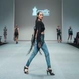 Ein Model steht am Ende eines Laufstegs, links und rechts sitzt das Publikum und im Hintergrund stehen weitere Models