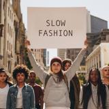 """Eine Gruppe junger Frauen läuft durch die Stadt, eine Frau in der Mitte hält ein Schild mit der Aufschrift """"Slow Fashion"""""""