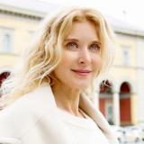 Eine blonde Frau mit weißem Mantel schaut in die Ferne