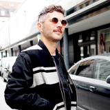 Oberkörperansicht von einem brünetten Mann mit einer schwarzen Jacke mit weißen Streifen und einer Sonnenbrille auf