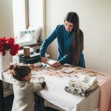 Eine Frau arbeitet an einem Tisch mit Stoffen und ein kleines Mädchen schaut dabei zu