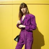Eine Frau mit einem violetten Overall steht vor einer gelben Wand