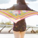 Rückenansicht auf eine Frau die hinter sich ein großes buntes Tuch gespannt in den Wind hält