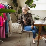 Eine Frau sitzt am Tisch und schaut über ihren Rücken aus dem Fenster, um sie herum hängen bunte Kleider und stehen viele Pflanzen