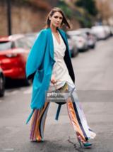 Eine brünette Frau mit einer bunten lockeren Hose und einem türkisen Mantel läuft über die Straße