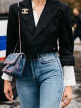Bildausschnitt einer Frau die eine Jeans und einen kurzen schwarzen Blazer auf einer weißen Bluse trägt