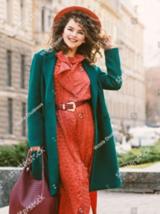 Eine brünette Frau mit rotem Kleid und einem grünen Mantel hält ihren roten Hut und lächelt in die Kamera