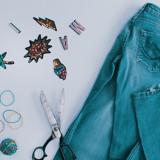 Auf einem Tisch liegen eine Jeans, eine Schere, Gummibänder und bunte Aufnäher