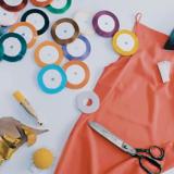 Ausschnitt eines Tischs auf dem ein Stück oranger Stoff, eine Schere, bunter Nähgarne, goldener Stoff und ein Bügeleisen liegen