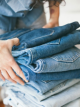 A close-up of a woman stacking a pile of jeans – reducing items is an important step in building a capsule wardrobe