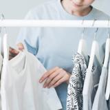 Eine Frau nimmt sich eine weißes Oberteil von einer Kleiderstande mit Oberteilen