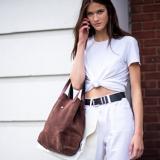 Eine brünette Frau mit einer weißen Hose und einem weißen T-Shirt, das am Bauch zusammengeknotet ist, hält sich ihr Handy ans Ohr