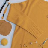 Ein gelber Pullover liegt ausgebreitet auf einer weißen Fläche daneben liegen Nähgarn, Ellebogenpatches, Nähnadeln und eine Schere