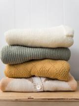 Ein Stapel mit Strickpullis – zur Pflege deiner Kleidung gehört auch, wie du sie aufbewahrst