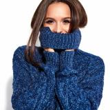 Eine brünette Frau hält sich den Rollkragen ihres blauen Pullovers vor ihr Gesicht