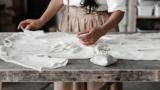 Eine Frau, die ein weißes Vintage-Kleid inspiziert