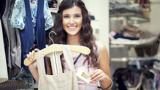Eine junge Frau, die sich das Etikett eines Kleidungsstücks ansieht, das sie vielleicht kaufen möchte