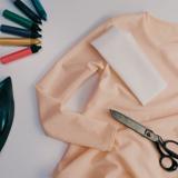 Ein helles Oberteil auf einer weißen Oberfläche mit einem Bügeleisen, bunten Stiften und einer Schere