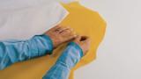 Schritt 2: Eine Frau legt Aufbügel-Deko auf die Flecken auf ihrem Kleid, um ihr Outfit wie neu aussehen zu lassen