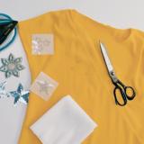 Ein gelbes T-Shirt auf einer weißen Oberfläche mit einem Bügeleisen, Sternstickern und einer Schere