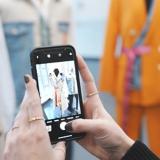 Sicht auf ein Handy mit dem ein Foto von einem Mantel mit verschiedenen Stoffen gemacht wird, im Hintergrund steht eine Schneiderpuppe mit einem orangen Blazer