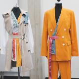 Zwei Schneiderpuppen, die Linke trägt einen Mantel aus verschiedenen Stoffen und die Rechte einen orangen Blazer und Hose