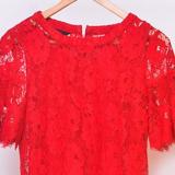 Frontansicht auf ein rotes Oberteil, daneben hängen bunte T-Shirts