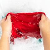 Ein rotes T-Shirt wird per Hand gewaschen