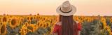 Eine Frau mit Strohhut läuft durch ein Feld voller  Sonnenblumen