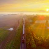 Eine Landschaft durch die eine Eisenbahn auf einer Strecke fährt und die Sonne im Hintergrund unter geht