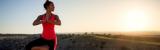 Junge Frau steht in einem Sportoutfit aus Elasthan auf einem Hügel und praktiziert Yoga im Sonnenaufgang.