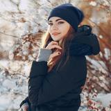 Junge Frau unternimmt in einer Daunenjacke einen Winterspaziergang