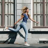 Eine Frau läuft mit großen Schritten an einer Häuserwand entlang