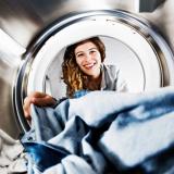 Sicht aus einer Waschmaschine mit Kleidung auf eine lächelnde Frau