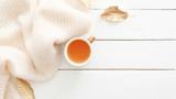Kuscheliger Pullover, arrangiert mit einer Tasse Tee
