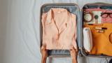 Frauenhände packen eine elegante, lachsfarbene Bluse aus Acetat in einen Koffer.