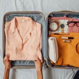Ein gepackter Koffer auf einem Bett mit heller Kleidung und Accessoires