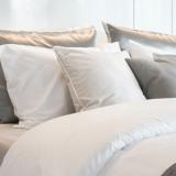 Ein ordentliches Bett mit vielen hellen Kissen und einer hellen Bettdecke