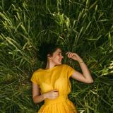 Eine Frau mit einem gelben Kleid liegt in einem Feld