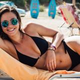 Eine junge Frau im Bikini liegt auf einer Sonnenliege