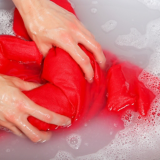Rote Kleidung wird mit den Händen gewaschen
