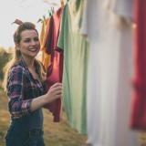Eine Frau hängt bunte Kleidung draußen an einer Wäschleine auf