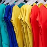 Türkise, blaue, gelbe und rote Oberteile an Kleiderbügeln