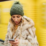 Eine Frau mit Pelzmantel schaut auf ihr Handy, im Hintergrund verschwommen fährt eine gelbe Bahn