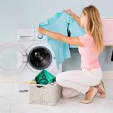 Eine Frau hockt vor einer Waschmaschine und hält ein hellblaues T-Shirt hoch