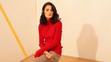 Eine junge Frau mit rotem Pullover sitzt auf einem Hocker
